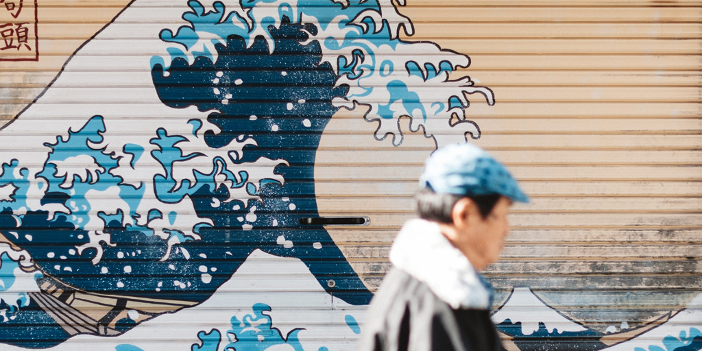 Photo: The Great Wave Off Kanagawa painted on a roller-door, with passerby  by Matthew Buchanan on Unsplash https://unsplash.com/photos/VVi59Xtsd8Y