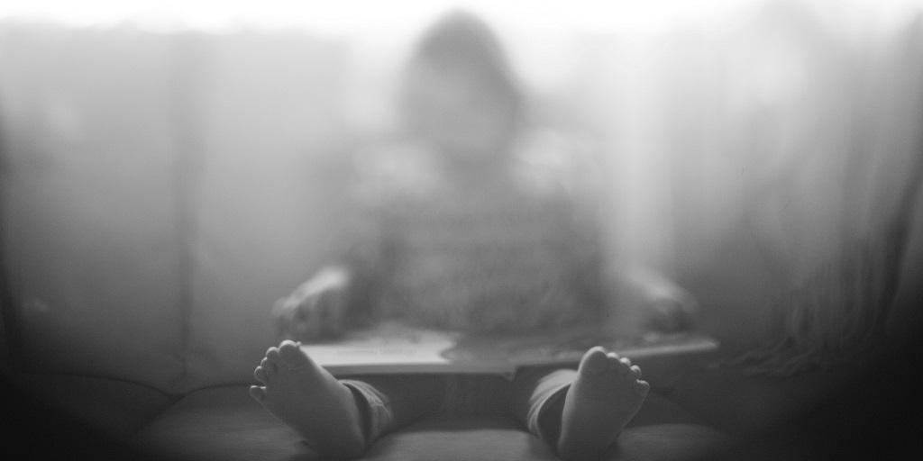 grey and blurred photo of a child on a couch, source: laura-fuhrman-696999-unsplash