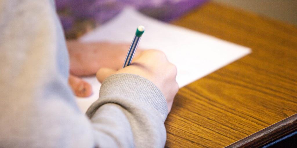 student writing on paper, source: ben-mullins-785450-unsplash