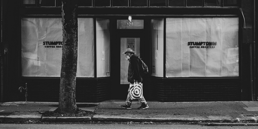 person passing by in front of a closed shop, source: sean-benesh-Zj3MDqyTIMM-unsplash